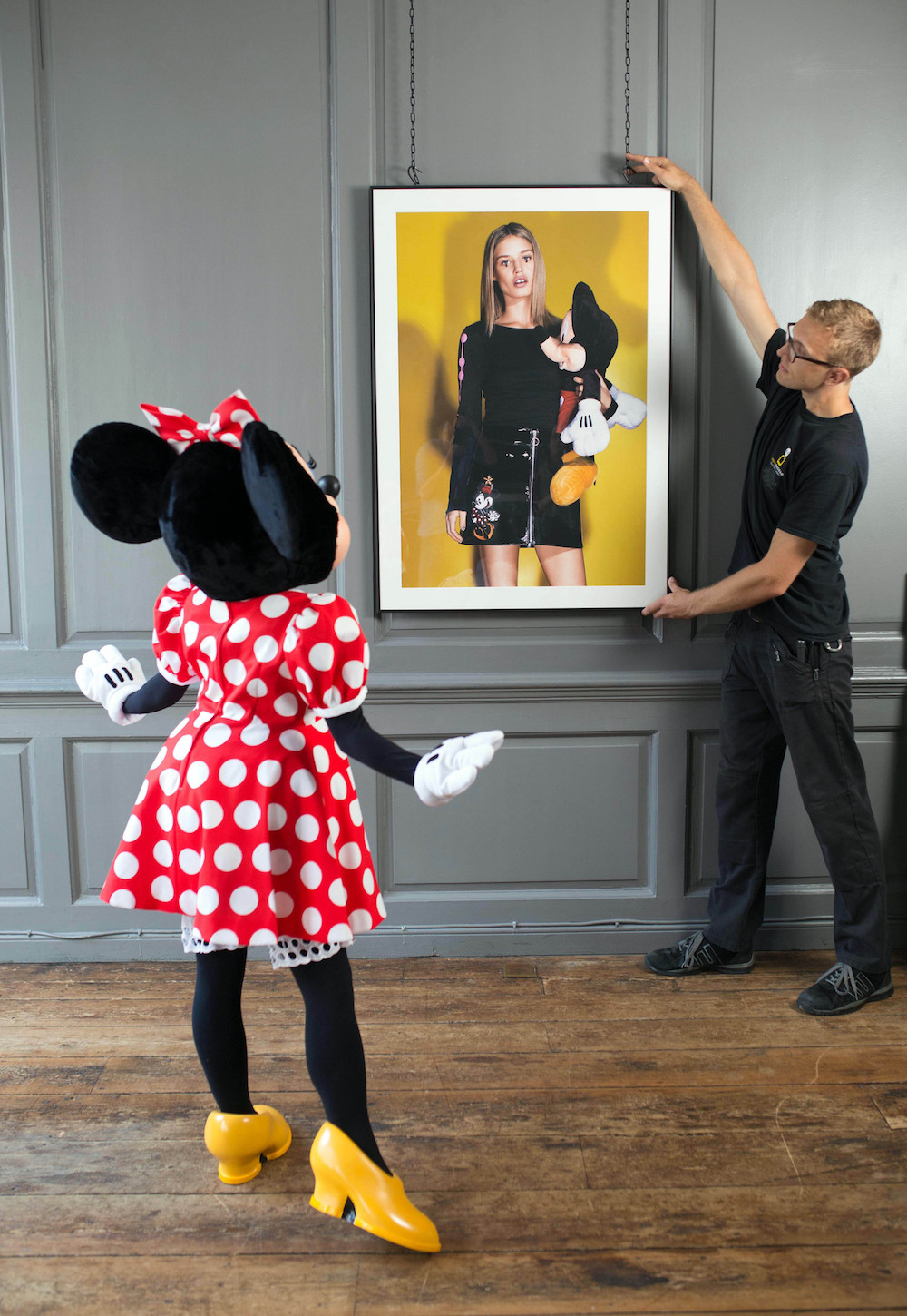 EDITORIAL USE ONLY Minnie Mouse watches as artwork is hung at Blacks Club in London, ahead of the opening of new exhibition, Minnie: Style Icon, in partnership with the British Fashion Council, which will be on display at the Soho venue during London Fashion Week. PRESS ASSOCIATION Photo. Picture date: Thursday September 17, 2015. The exhibition of exclusive photographs, exploring the character of Disney's Minnie Mouse and her influence on fashion and pop culture, has been curated with the help of model and photographer, Georgia May Jagger. Photo credit should read: David Parry/PA Wire